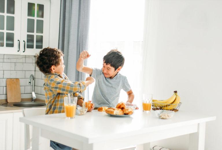 deux enfants se chamaillent à table dans une cuisine