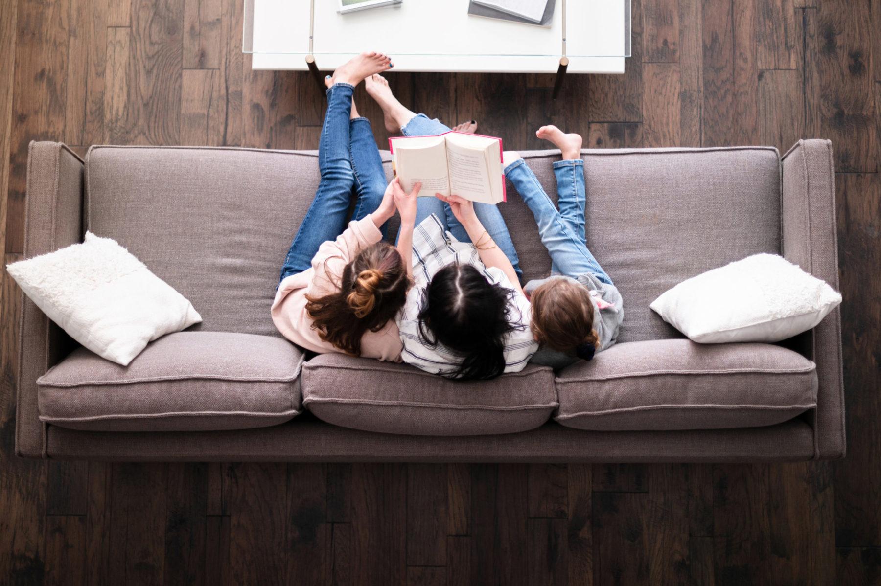 vue d'un canapé avec famille qui lit tranquillement