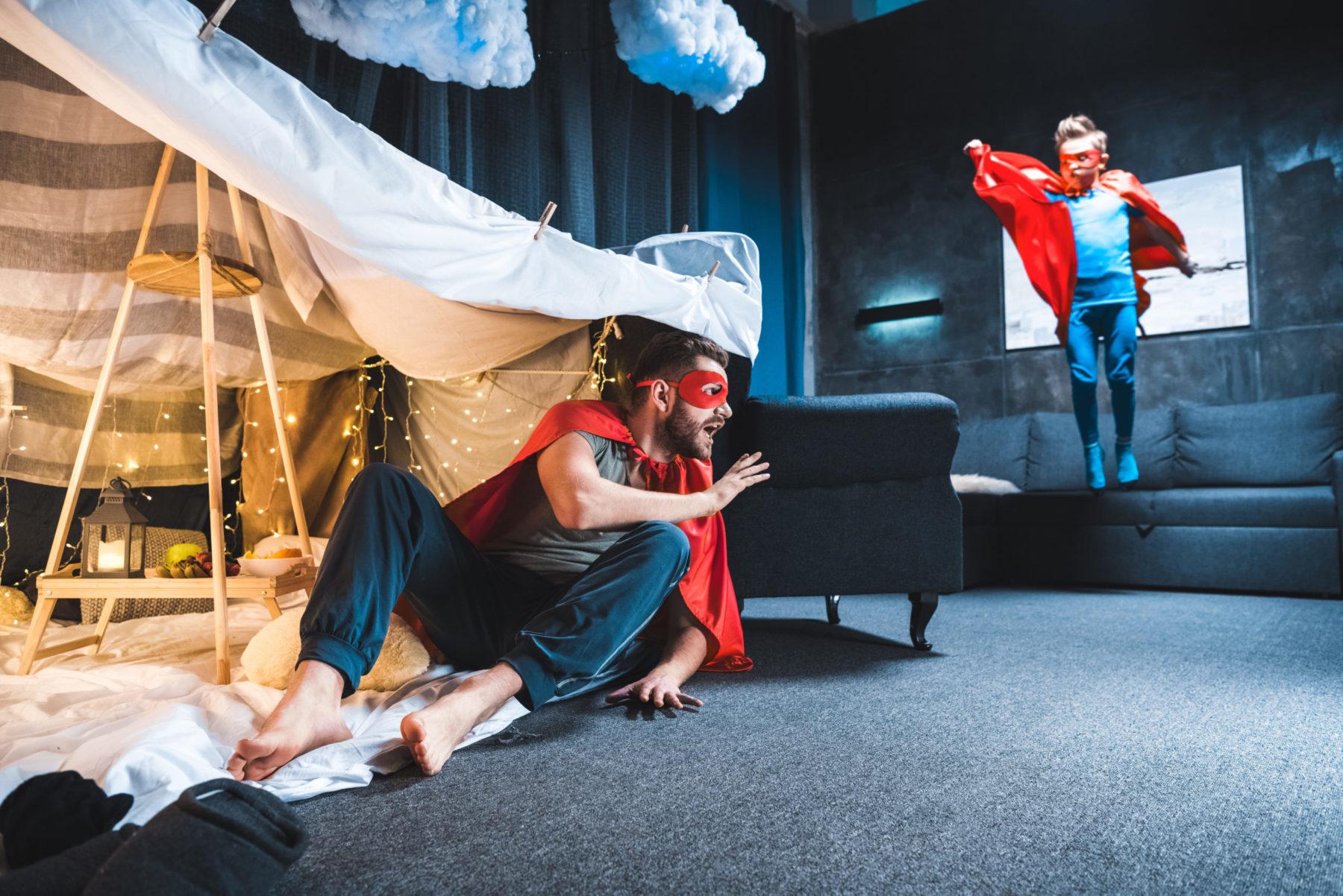 Pères et fils jouant aux super héros dans une chambre