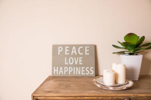 bougies posées sur une commode avec un cadre peace love happiness